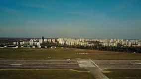 WARSAW, POLAND - APRIL, 1, 2017. Aerial shot of a small propeller aircraft landing on city airport plated runway on a Royalty Free Stock Images