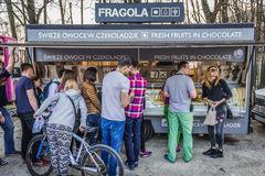 Food truck festival. Warsaw, Poland - April 1, 2017: People in front of food truck with fruit in chocolate during food festival in Warsaw Stock Images