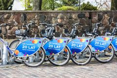Row of city bikes for rent at docking stations in Old town, Warsaw. Warsaw, Poland - April 23, 2017: Row of city bikes for rent at docking stations in Old town Royalty Free Stock Photos