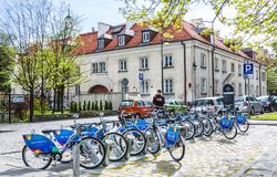 Row of city bikes for rent at docking stations in Old town, Warsaw. Warsaw, Poland - April 23, 2017: Row of city bikes for rent at docking stations in Old town Royalty Free Stock Photo