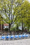 Row of city bikes for rent at docking stations in Old town, Warsaw. Warsaw, Poland - April 23, 2017: Row of city bikes for rent at docking stations in Old town Stock Photography
