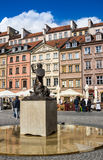 Warsaw, Poland - April 23, 2017: Statue of Mermaid Syrenka - symbol of Warsaw at Old Town Market Square against tenements and re Royalty Free Stock Photography
