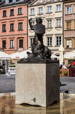 Warsaw, Poland - April 23, 2017: Statue of Mermaid Syrenka - symbol of Warsaw at Old Town Market Square against tenements and re Stock Images