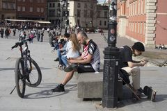 Warsaw`s Old Town Market Place on a sunny day. Tourists are reading. WARSAW, POLAND - APRIL 28, 2018: Warsaw`s Old Town Market Place on a sunny day. Tourists are royalty free stock image