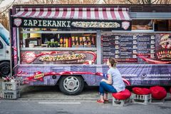 Food truck festival. Warsaw, Poland - April 1, 2017: Woman sits in front of food truck with polish Zapiekanki - long open faced cheese sandwiches during food Royalty Free Stock Photos