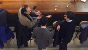 WARSAW, POLAND - DECEMBER, 22, 2016. Mid-aged businessmen having conversation at the bar, top view shot Royalty Free Stock Photo