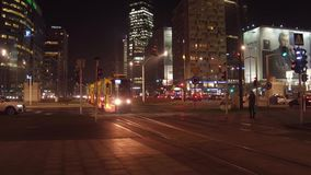 WARSAW, POLAND - DECEMBER, 22, 2016. Modern trams and night traffic at busy urban interection. 4K pan shot. WARSAW, POLAND - DECEMBER, 22, 2016. Modern trams and stock video footage