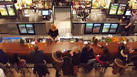 WARSAW, POLAND - DECEMBER, 21, 2016. People drinking and hanging out at the bar. Top shot Stock Images