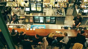 WARSAW, POLAND - DECEMBER, 21, 2016. People drinking and hanging out at the bar. View from above shot Royalty Free Stock Photo