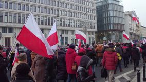 WARSAW, POLAND - DECEMBER, 17, 2016. People with Polish flags marching in the street Royalty Free Stock Images