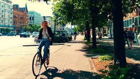 WARSAW, POLAND - JULY 11, 2017. Beautiful young woman cycling along urban bike road in city center Royalty Free Stock Images