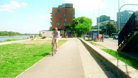 Warsaw, Poland - July 11, 2017. People cycling along the city bike road. Warsaw, Poland - July 11, 2017. People cycling along the city bike path stock footage