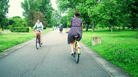 WARSAW, POLAND - JULY 11, 2017. Women cycling along park road Royalty Free Stock Images