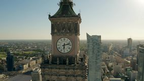 WARSAW, POLAND - JUNE 5, 2019. Aerial shot of the clock on famous Palace of Culture and Science and the cityscape stock video footage