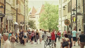 WARSAW, POLAND - JUNE 10, 2017. Tourists walk along old town street on a summer sunny day Stock Photo