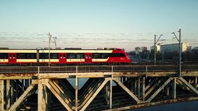 WARSAW, POLAND - MARCH, 27, 2017. Aerial shot of red passenger train moving on railway bridge across the river Stock Images