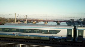 WARSAW, POLAND - MARCH, 27, 2017. Aerial tracking shot of modern passenger train moving on railway bridge across the. River. 4K video stock video footage