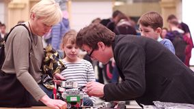 WARSAW, POLAND - MARCH, 4, 2017. Small DIY robot and family supporting young participant of robotics competition. WARSAW, POLAND - MARCH, 4, 2017. DIY robot and royalty free stock images
