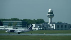 Free WARSAW, POLAND - MAY, 18, 2017. LOT Polish Airlines Airplane Takeoff And Chopin Airport Control Tower Beyond Runway Heat Stock Image - 92873251