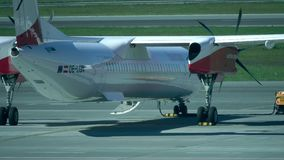 WARSAW, POLAND - MAY, 18, 2017. Parked Austrian Airlines Bombardier propeller plane at Chopin airport. 4K video. WARSAW, POLAND - MAY, 18, 2017. Parked Austrian stock video footage