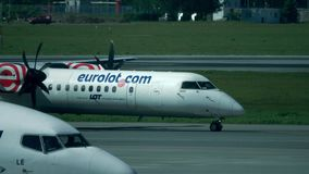 WARSAW, POLAND - MAY, 18, 2017. Telephoto lens pan shot of taxiing Eurolot Bombardier propeller airplane. WARSAW, POLAND - MAY, 18, 2017. Telephoto lens pan shot stock image