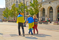 WARSAW, POLAND. The young people who are wrapped up in the Ukrainian flags go down the street Stock Photos