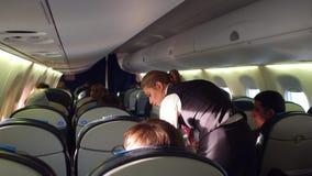 WARSCHAU, POLEN - DEZEMBER, 24 VERLOSEN Sie weiblichen Flugbegleiter an den Arbeits- und Passagierflugzeugpassagieren in der Kabi Stockbild
