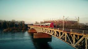 WARSCHAU, POLEN - MÄRZ, 27, 2017 Luftschuß des roten Personenzugs Eisenbahnbrücke gegen moderne Arena weiter gehend Stockbild