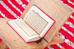 Warsh quran open on a wooden stand. On a red Moroccan rug Stock Photography
