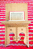 Warsh quran open on a wooden stand. On a red Moroccan rug Royalty Free Stock Image