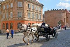 Warshau, Polen De bemanning van het toeristenpaard tegen de achtergrond van een barbacane Royalty-vrije Stock Foto's
