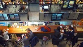 WARSHAU, POLEN - DECEMBER, 17, 2016 Jongeren die en uit bij de bar eten hangen Hoogste meningsschot Royalty-vrije Stock Foto's