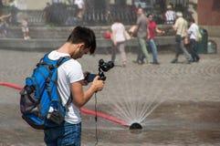 Warshau, Polen - Juni 23, 2016 Toeristen met steadicam, tegen de achtergrond van een tijdelijke fontein in de hoofdstad van Polen Stock Afbeelding