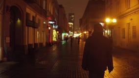 WARSHAU, POLEN - NOVEMBER, 28, 2016 De oude voetgangers van de stadsstraat bij nacht 4K steadicam bokeh achtergrondvideo stock videobeelden