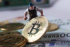 WARSHAU/POLEN - September 23 2018: bitcoins nieuwe virtuele munt Een arbeider graaft op gouden bitcoin met dollarachtergrond royalty-vrije stock afbeeldingen
