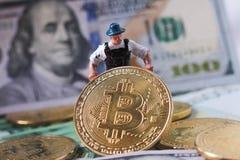 WARSHAU/POLEN - September 23 2018: bitcoins nieuwe virtuele munt Een arbeider graaft op gouden bitcoin met dollarachtergrond stock fotografie