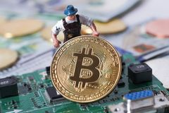 WARSHAU/POLEN - September 23 2018: bitcoins nieuwe virtuele munt Een arbeider graaft op gouden bitcoin met dollarachtergrond stock foto