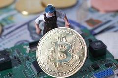 WARSHAU/POLEN - September 23 2018: bitcoins nieuwe virtuele munt Een arbeider graaft op gouden bitcoin met dollarachtergrond royalty-vrije stock foto's