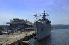 Warship docked at passenger terminal Stock Photo