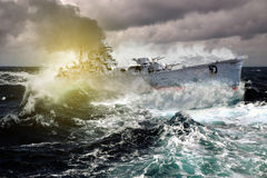 Warship sailing in a stormy sea. Waves creating cutting spray royalty free stock images