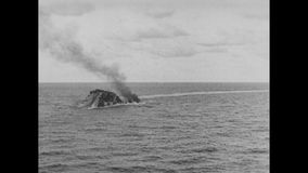Warship sinking and exploding into the ocean, 1940s stock video footage