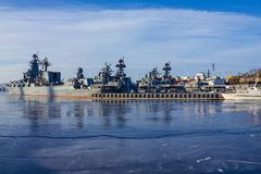 Warships in the cold sea. Gray ships, a military squadron near the coast of the city. Navy, the place of basing. Cold weather, the sea is covered with ice Stock Photo
