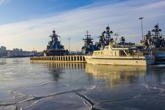 Warships in the northern harbor. Military destroyers, the flotilla stands in the roadstead in the seaport. Cold season, the water is covered with a thin layer Royalty Free Stock Image