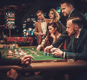 Warstwa wyższa przyjaciele uprawia hazard w kasynie obraz stock