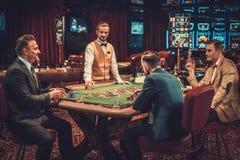 Warstwa wyższa przyjaciele uprawia hazard w kasynie zdjęcia stock