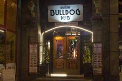 WARSZAWA POLEN - JANUARI 02, 2016: Ingång till den brittiska bar- och stekhusbulldoggen på den snowless vinternatten Fotografering för Bildbyråer