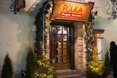 WARSZAWA POLEN - JANUARI 01, 2016: Ingång till den traditionella polska kokkonstpolkan för restaurang i julgarnering på natten royaltyfri fotografi
