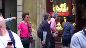 WARSZAWA POLEN - JUNI 10, 2017 Asiatiska turister går i traditionella smycken shoppar Arkivfoto