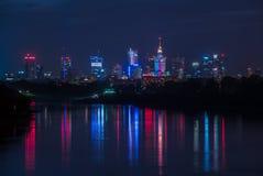Warszawa/Polen - Oktober 7 2018 Nattsikt på de i stadens centrum stadsbyggnaderna med färgrik ljusreflexion i floden arkivfoto