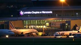 WARSZAWA POLEN - SEPTEMBER 14, 2017 Kommersiella flygplan på den internationella Chopin flygplatsterminalen på natten Arkivfoton